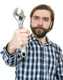 De jonge gebaarde man een holdingsmoersleutel ter beschikking Stock Afbeeldingen