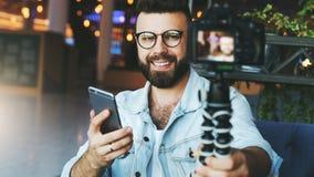 De jonge gebaarde mannelijke video blogger leidt tot videoinhoud voor zijn kanaal De gelukkige kerel schiet video stromend voor g stock foto's
