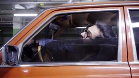 De jonge gebaarde mens met lang donker haar opent rood autoraam en kijkt uit het stock footage
