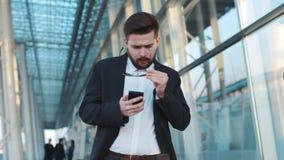 De jonge gebaarde mensengangen door de luchthaventerminal, merkt smth op zijn telefoon op, opstijgt de zonnebril in verrassing stock footage