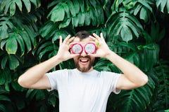 De jonge gebaarde plakken van de mensenholding van Pitaya-draakfruit voor zijn ogen, luid lachen uit royalty-vrije stock foto