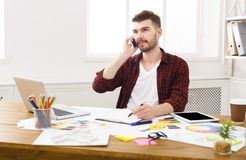 De jonge geconcentreerde ontwerper heeft mobiele telefoonbespreking Stock Afbeelding