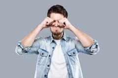 De jonge gedeprimeerde mens die aan bezorgdheid lijden behandelt zijn gezicht over grijze achtergrond stock afbeeldingen