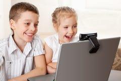 De jonge geitjes communiceren online met Stock Afbeeldingen
