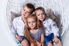De jonge geitjes die samen de broerszusters zitten van jongensmeisjes kijken blauwe ogen stock foto's