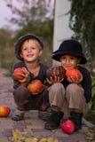 De jonge geitjes die van Nice met Halloween-pompoenen zitten Royalty-vrije Stock Fotografie