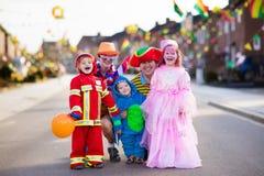 De jonge geitjes en de ouders op Halloween-truc of behandelen stock foto's