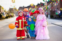 De jonge geitjes en de ouders op Halloween-truc of behandelen royalty-vrije stock fotografie