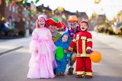 De jonge geitjes en de ouders op Halloween-truc of behandelen royalty-vrije stock foto's