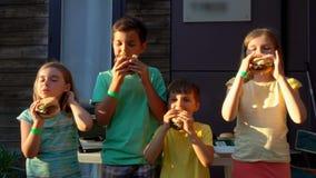 De jonge geitjes eten hamburgers stock videobeelden