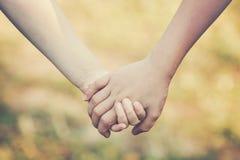 De jonge geitjes` handen die voor steun en vriendschap houden, vertroebelen groen gras royalty-vrije stock foto's