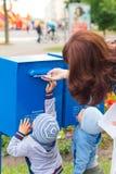 De jonge geitjes helpt haar moeder zet brieven in de brievenbus Stock Foto