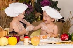 De jonge geitjes kleedden zich als chef-koks het koken Stock Foto's