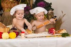 De jonge geitjes kleedden zich als chef-koks het koken Stock Afbeelding