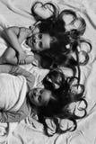 De jonge geitjes met gelukkige gezichten en het hart gevormde haar hebben rust in bed Kinderjaren en liefdeconcept Meisjes op wit Stock Afbeeldingen