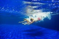 De jonge geitjes met moeder duiken in zwembad stock afbeeldingen