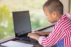 De jonge geitjes onderzoeken Internet en oude laptops stock foto