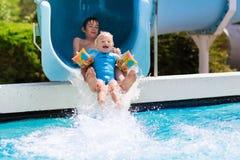De jonge geitjes op een water glijden binnen zwembad Royalty-vrije Stock Afbeeldingen