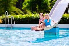De jonge geitjes op water glijden binnen zwembad stock fotografie