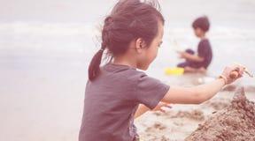 De jonge geitjes speelt op het strand, maakt het meisje zandkasteel op de voorgrond royalty-vrije stock fotografie