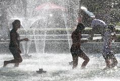 De jonge geitjes spelen in een water van een fontein op een zonnige de zomerdag tijdens de zomeronderbreking in Sofia, Bulgarije  Royalty-vrije Stock Foto's