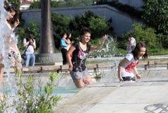 De jonge geitjes spelen in een water van een fontein op een zonnige de zomerdag tijdens de zomeronderbreking in Sofia, Bulgarije  Stock Foto