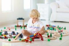 De jonge geitjes spelen houten spoorweg Kind met stuk speelgoed trein royalty-vrije stock afbeeldingen