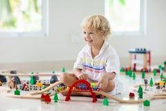 De jonge geitjes spelen houten spoorweg Kind met stuk speelgoed trein royalty-vrije stock afbeelding