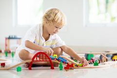 De jonge geitjes spelen houten spoorweg Kind met stuk speelgoed trein royalty-vrije stock fotografie