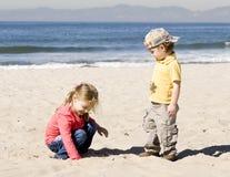 De jonge geitjes spelen met een zand Stock Fotografie