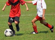 De jonge geitjes spelen voetbal stock afbeelding