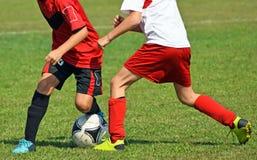 De jonge geitjes spelen voetbal stock foto's