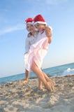 De jonge geitjes van de kerstman bij het de zomerstrand Stock Foto's