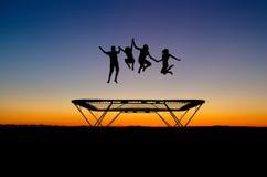 De jonge geitjes van de zonsondergang op trampoline stock foto