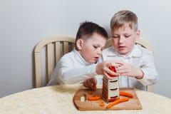 De jonge geitjes verpletterden gekookte wortelen in de keuken stock afbeelding