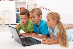 De jonge geitjes vonden iets interesserend op laptop Stock Foto
