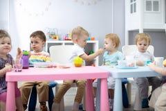 De jonge geitjesgroep heeft lunch in kleuterschool Leuke kindjongen die een maaltijdmeisje delen stock foto's