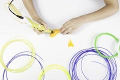 De jonge geitjeshand die gele 3D drukpen met gloeidraden houden en maakt hart Royalty-vrije Stock Foto's