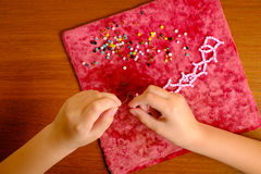 De jonge geitjeshanden verzamelen roze parels op het drawstring Stock Foto