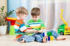 De jonge geitjesjongens spelen samen met onderwijsspeelgoed Royalty-vrije Stock Afbeeldingen