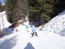 De jonge geitjesmanoeuvre van de skischool op een ijzige weg Stock Afbeeldingen