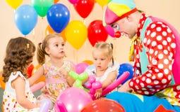 De jonge geitjesmeisjes en clown van kinderen op verjaardagspartij Stock Foto's