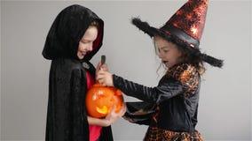 De jonge geitjestruc of behandelt De jongen en het meisje in kostuums voor HalloweenGirl houden snoepjes in handen De jongen houd stock video