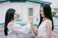 De jonge gelukkige Aziatische meisjes beste vrienden glimlachen zich samen het verenigen en het schudden handen, het teken van de stock afbeelding