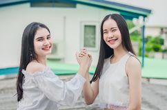 De jonge gelukkige Aziatische meisjes beste vrienden glimlachen zich samen het verenigen en het schudden handen, het teken van de royalty-vrije stock afbeeldingen