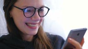 De jonge gelukkige donkerbruine vrouw in glazen typt een bericht op een mobiele telefoon stock videobeelden
