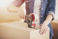 De jonge gelukkige dozen van de vrouwenverpakking Het bewegen zich, aankoop van nieuwe woning stock foto's