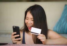 De jonge gelukkige en mooie Aziatische Chinese creditcard van de vrouwenholding gebruikend mobiele telefoon voor Internet-bankwez royalty-vrije stock foto's