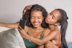 De jonge gelukkige en mooie Aziatische zusters of de meisjes koppelen het glimlachen vrolijke nemende selfie foto thuis aan mobie royalty-vrije stock afbeeldingen