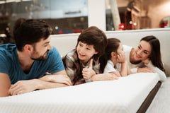 De jonge gelukkige familie controleert op zachtheid die van orthopedische matras, op bed in meubilairopslag liggen stock afbeeldingen